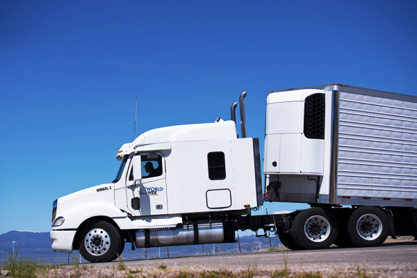 Big white truck with a trailer and a refrigeration unit on the road of the highway against the blue clear sky. Side view draws all the outlines of the modern powerful truck with chrome pipes.